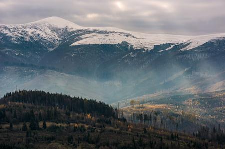 森と丘の上雪の上と山。曇り空を印象的な光のビームを持つ素敵な後半の秋の風景