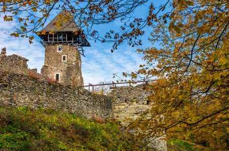 Nevytsky Castle, Ukraine - October 27, 2016: tower with wooden roof and stone wall of fortress on grassy hillside among forest with yellow foliage in autumn. popular tourist attraction