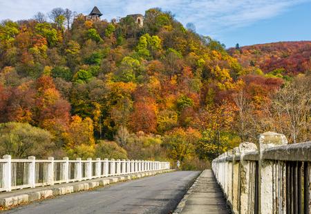 Nevytsky Castle, Ukraine - October 27, 2016: bridge to Nevytsky Castle hill with yellow foliage in autumn forest. popular tourist attraction Stock Photo