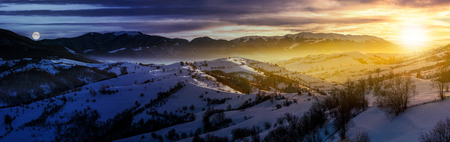 day and night time change concept in gorgeous panorama of mountainous countryside in winter. snow covered rural area on rolling hills and huge mountain ridge in a distance. fantasy world 版權商用圖片 - 87666587