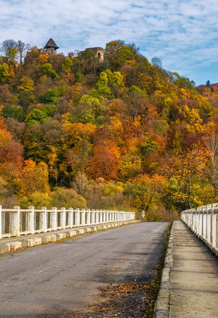 bridge to Nevytsky Castle hill with yellow foliage in autumn forest. popular tourist attraction
