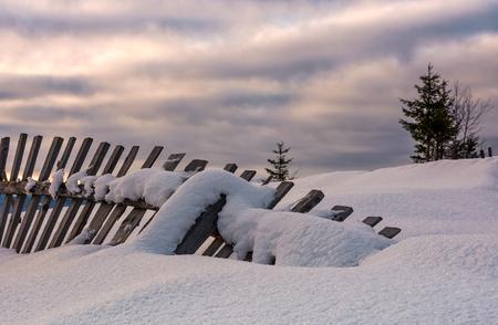 눈 덮인 언덕에 타락 한 나무 울타리입니다. 겨울의 아름다운 농촌 풍경 스톡 콘텐츠