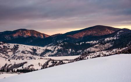 눈 덮인 언덕 일출 산속에. 흐린 하늘 Carpathians에서 화려한 겨울 풍경 스톡 콘텐츠