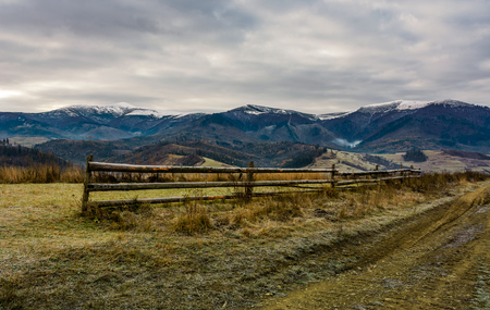 fence on grassy meadow in autumn. landscape of mountain ridge with snowy tops in the distance. gorgeous and unusual countryside scenery Stock Photo