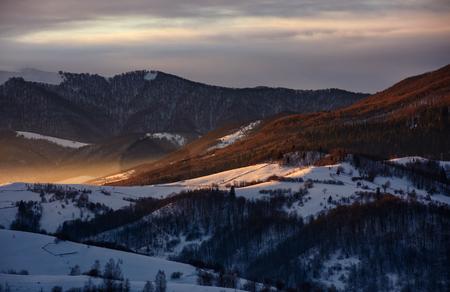 豪華な赤い日の出の森で雪の山丘。冬の美しい自然風景