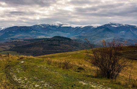Weg durch Hügel im Herbst. Bergrückenlandschaft mit schneebedeckten Gipfeln in der Ferne. wunderschöne und ungewöhnliche Landschaft im Herbst Standard-Bild - 87863163