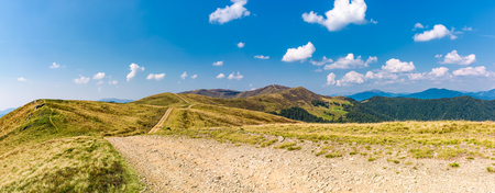 panoramic view of path through the mountain ridge. spectacular landscape in early autumn weather with fluffy clouds on the blue sky Stock Photo