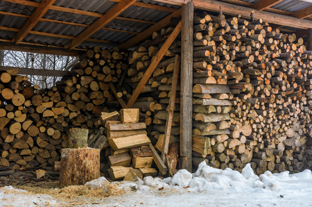 woodshed full of chopped firewood. beautiful scene of everyday rural life in winter. ecological energy concept Stock Photo
