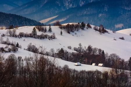 冬の雪に覆われた丘の上の村。日の出山地の美しい田舎の風景 写真素材