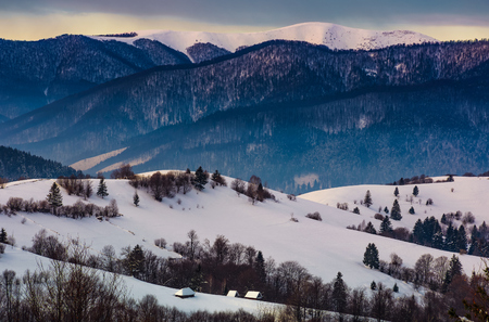 gorgeous winter landscape in mountainous rural are. beautiful countryside scenery with village and forest on snow covered rolling hills at sunrise