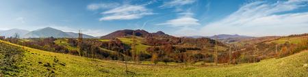 秋に中山間地域のパノラマ。山の尾根や森山の斜面の紅葉が楽しめる美しい田園風景