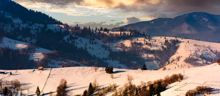 gorgeous winter landscape in mountainous rural are. beautiful panoramic countryside scenery with village and forest on snow covered rolling hills at sunrise Stock Photo