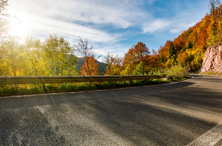 asphalt road through autumn forest in mountains. beautiful and colorful scenery on sunny day under the blue sky with some clouds Stock Photo