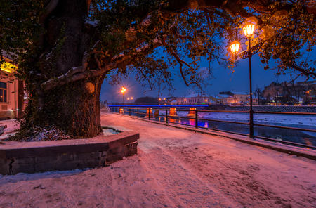huge tree and lantern on the winter embankment. beautiful evening on the river with some ice and snow on the shore Stock Photo - 89004424