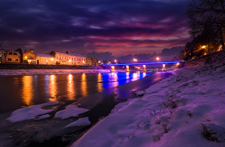 gorgeous evening cityscape of old european town Uzhgorod in winter. beautiful cloudy sky over the river Uzh with some ice and snow on the shore. citylights reflect on the water surface