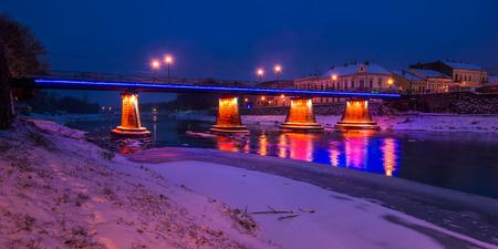 Panorama da ponte através do rio Uzh à noite. bela paisagem urbana da antiga cidade europeia Uzhgorod no inverno Foto de archivo - 89004423