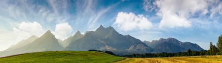 夏の間タトラ山脈の近くの地方の野原。農業地域の美しいパノラマ。岩の多い峰がある豪華な山の尾根 写真素材