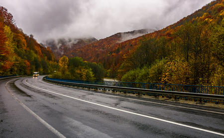 curve road through mountains on autumn rainy day. overcast sky over the forest in red foliage. yellow bus, with turned lights, ride on wet asphalt Stock Photo