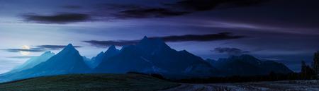 夏のタトラ山脈の近くの田園地帯、夜。農業地域の美しいパノラマ。岩の多い峰がある豪華な山の尾根 写真素材