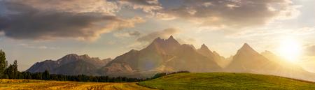 일몰시 여름에 Tatra 산맥 근처 시골 필드. 농업 지역의 아름 다운 파노라마입니다. 높은 바위 봉우리가있는 화려한 산 능선 스톡 콘텐츠