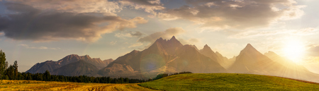 rural fields near Tatra Mountains in summer at sunset. beautiful panorama of agricultural area. gorgeous mountain ridge with high rocky peaks Stock Photo