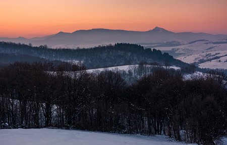 beautiful reddish winter dusk in mountains with high peak. dark leafless forest on snow covered hills