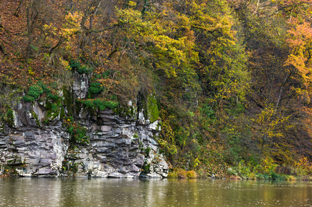 rocky cliff over the river in forest. beautiful autumn background with lots of textures Stock Photo