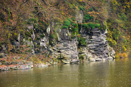 rocky cliff over the river in forest. beautiful autumn background with lots of textures Stock fotó