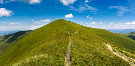 山の尾根の芝生の頂上を通る歩道。天気の良い日と青空がいくつかの雲で、夏の風景のゴージャスなパノラマ。ハイキング先のコンセプト 写真素材