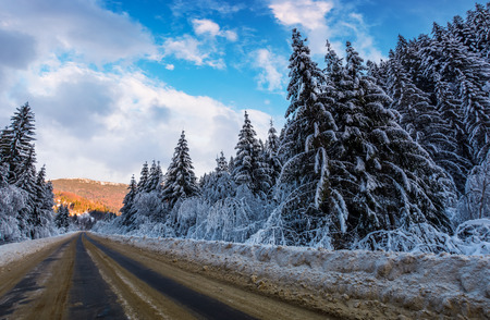 snowy road through mountains in evening. wonderful nature scenery in winter Stock Photo