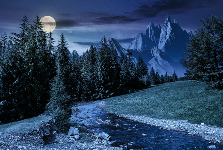 fairy tale mountainous summer landscape at night in full moon light. composite image with high rocky peaks above the mountain river in spruce forest