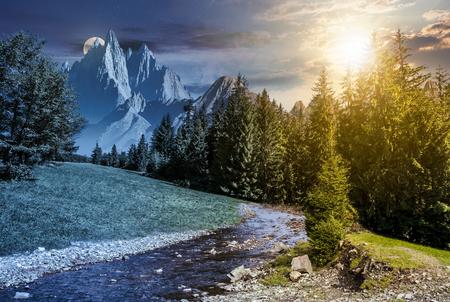 満月の光の中で夜のおとぎ話山岳地帯の夏の風景。スプルースフォレストの山の川の上に高い岩のピークを持つコンポジット画像。昼と夜の時間変