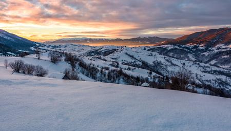 山岳地帯の冬の田園地帯で豪華な朝。谷の空と青の影に美しい赤みがかった雲