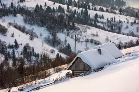 깊은 눈에 언덕에 우드. 산악 마 외곽에서 아름 다운 겨울 농촌 풍경 일출