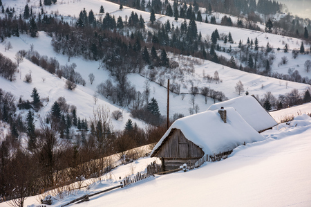 woodshed on hillside in deep snow. beautiful winter rural scenery in the mountainous village outskirts at sunrise