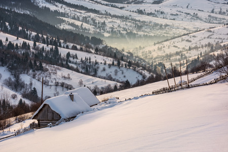 woodshed on hillside in deep snow. beautiful winter rural scenery in the mountainous village outskirts at foggy sunrise Stock Photo