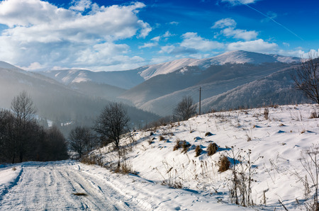 rural road in snowy mountainous area. beautiful winter scenery on a bright sunny day. mountains with snowy tops in a far distance Stock Photo