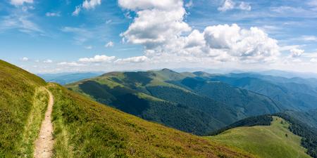 晴れた夏の日に美しい山岳風景。青空の下の草の中腹を走る歩道、ふわふわの雲。山の尾根のゴージャスなパノラマ 写真素材