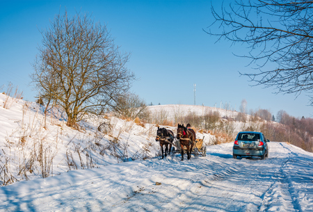 Pilipets, Ukraine - December 21, 2016: traffic in mountainous rural area in winter. cart with two horses and small car pass each other on snowy countryside road