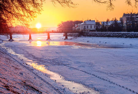 winter sunrise on the bank of ice covered river Uz. Sun over the bridge of old European town Uzhgorod Stock Photo