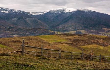 Holzzaun auf Hügeln der Gebirgslandschaft. landwirtschaftliche Felder im Spätherbst trübes Wetter. Bergrücken mit schneebedeckten Gipfeln in der Ferne Standard-Bild - 89218106