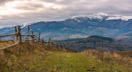 Holzzaun auf Hügeln der Gebirgslandschaft. landwirtschaftliche Felder im Spätherbst trübes Wetter. Bergrücken mit schneebedeckten Gipfeln in der Ferne Standard-Bild - 89218108