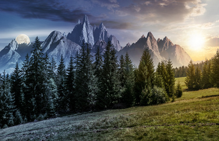 day and night time change concept. spruce forest on grassy hillside in mountains with rocky peaks. gorgeous composite image of summer landscape with sun and moon. Stock Photo