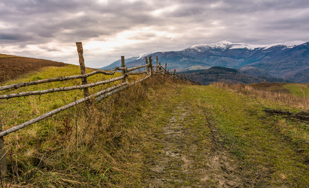 fence along dirt road in mountainous rural area. agricultural fields on hills in late autumn. mountain ridge with snowy tops in the distance