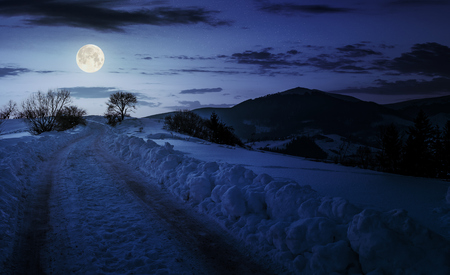 countryside road uphill in snow at night in full moon light. beautiful winter scenery in mountainous area Stock Photo