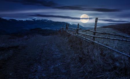 보름달 빛에서 밤 산악 시골에서 나무 울타리. 눈 덮인 길어야와 산 능선 스톡 콘텐츠 - 89218117