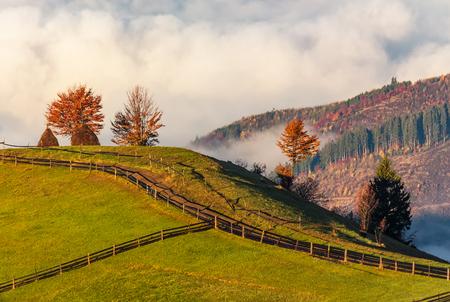 안개가 자욱한 산에서 경로 따라 울타리입니다. 단풍 전원 풍경의 화려한 일출
