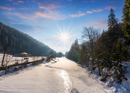 frozen river in forested mountains. beautiful scenery with spruce trees and village on the banks Banco de Imagens