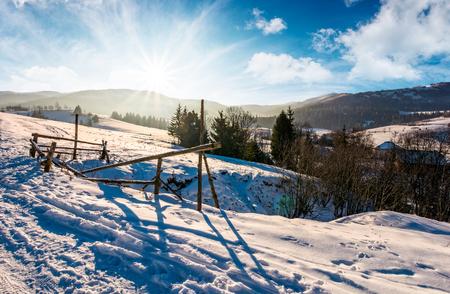 시골에서 눈 덮인 슬로프에 울타리를 고장. 산 능선 위에 밝은 태양이 함께 사랑스러운 겨울 풍경