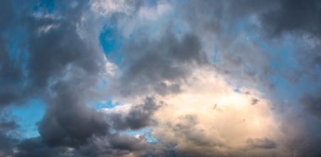 panorama of gorgeous cloudscape at dusk. heavy autumn clouds lit by the last rays of sun